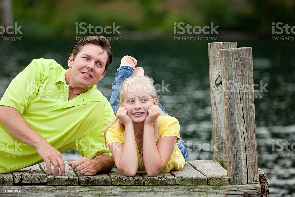 Father and Daughter Laying on a Dock royalty-free stock photo