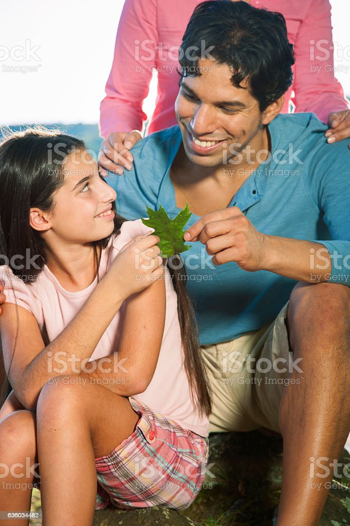 Father and daughter looking at leaf stock photo
