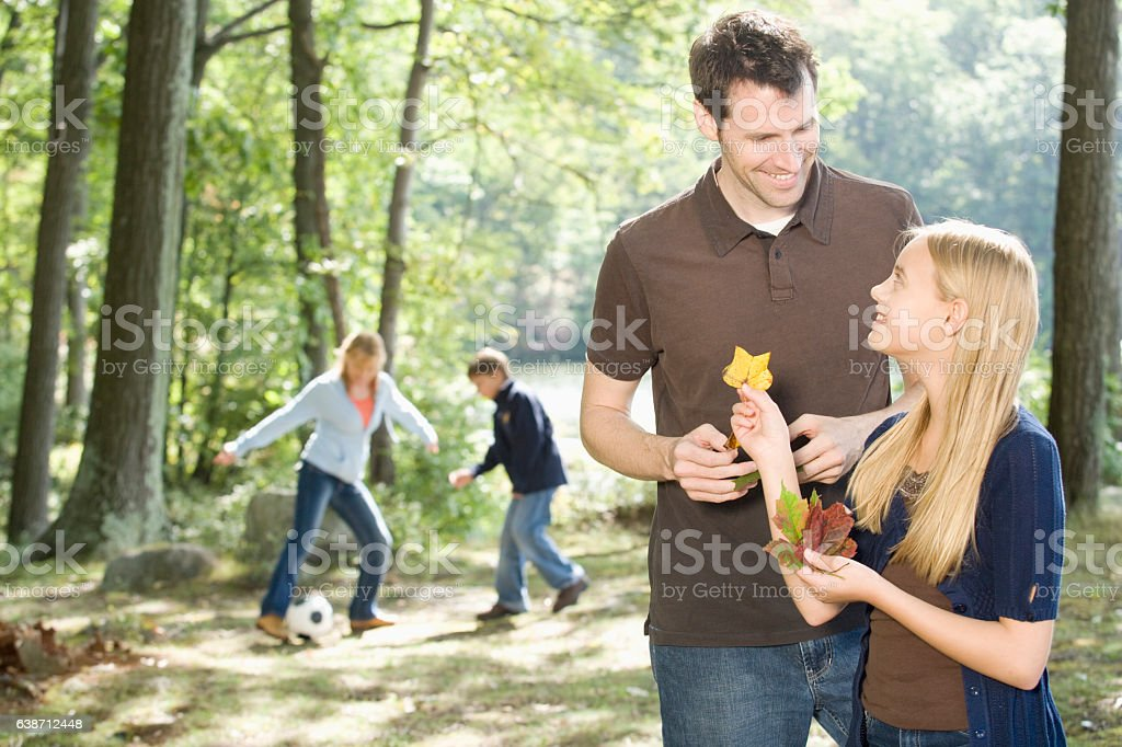 Father and daughter looking at leaves together in nature stock photo