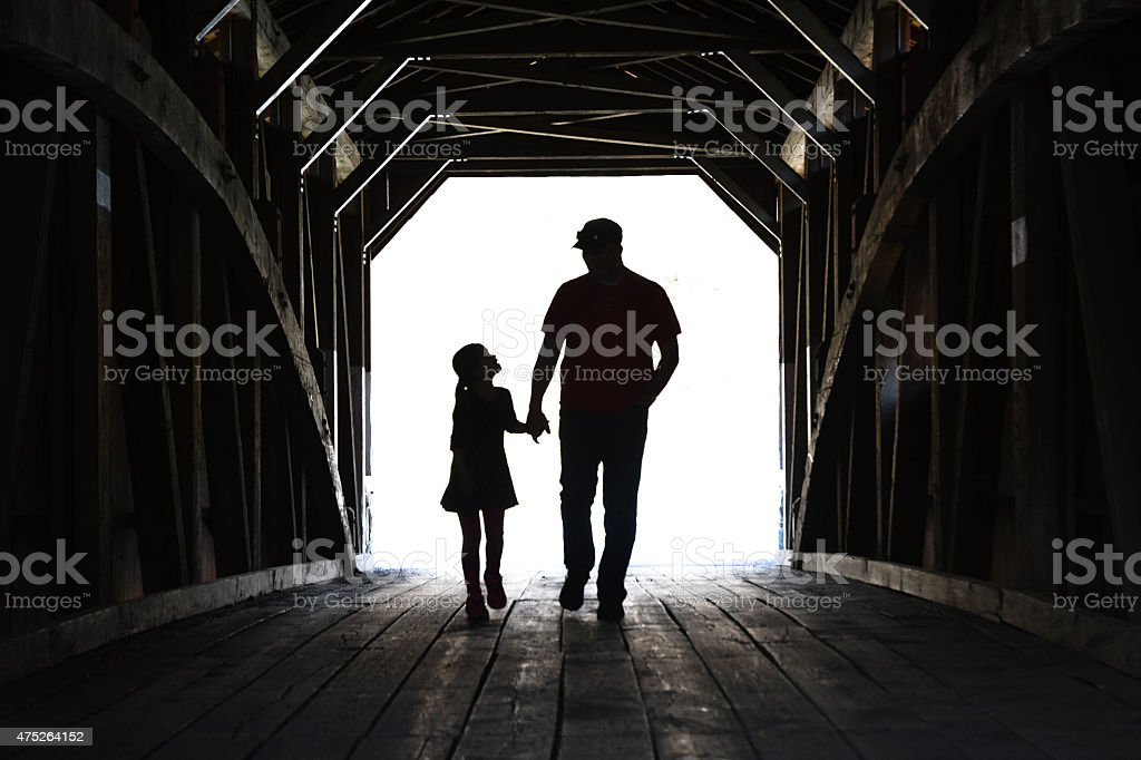 Father And Daughter On A Covered Bridge stock photo