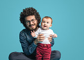 Father and daughter on blue background, Smiling portrait