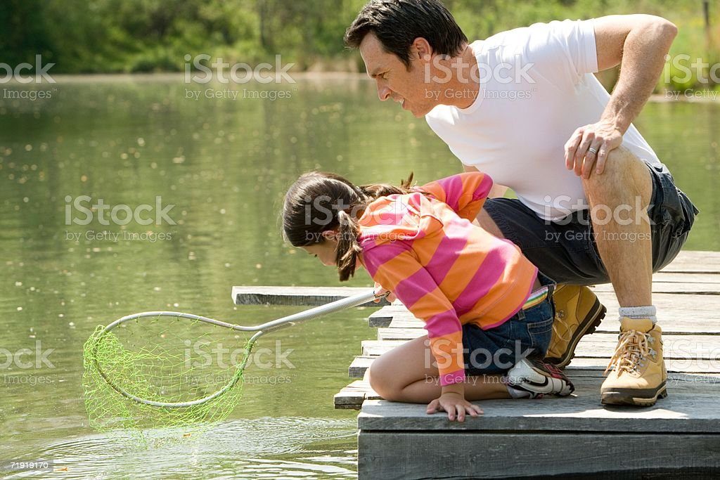 Father and daughter on jetty, holding fishing net stock photo