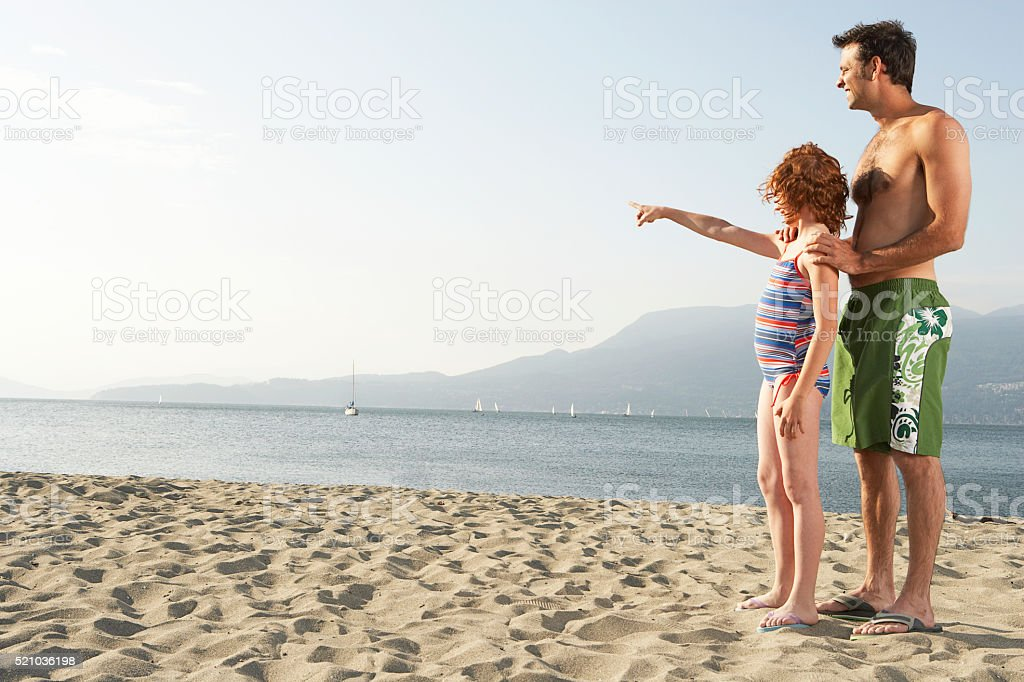 Father and daughter on the beach stock photo