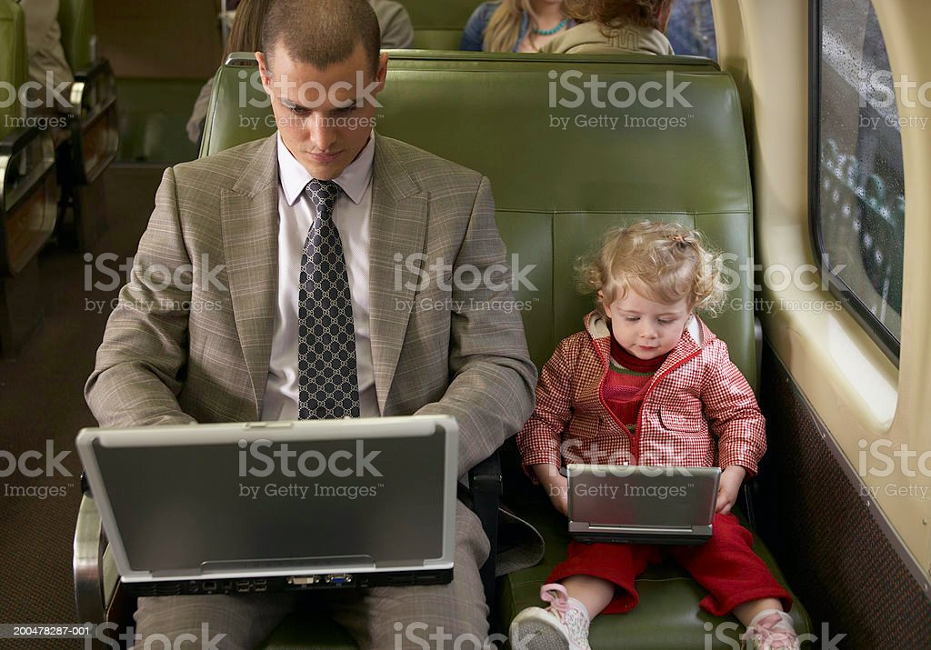 Father and daughter (1-3) on train using laptop and DVD player royalty-free stock photo
