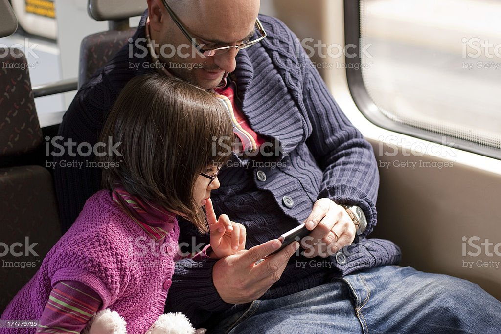 Father and daughter on train with smart phone royalty-free stock photo