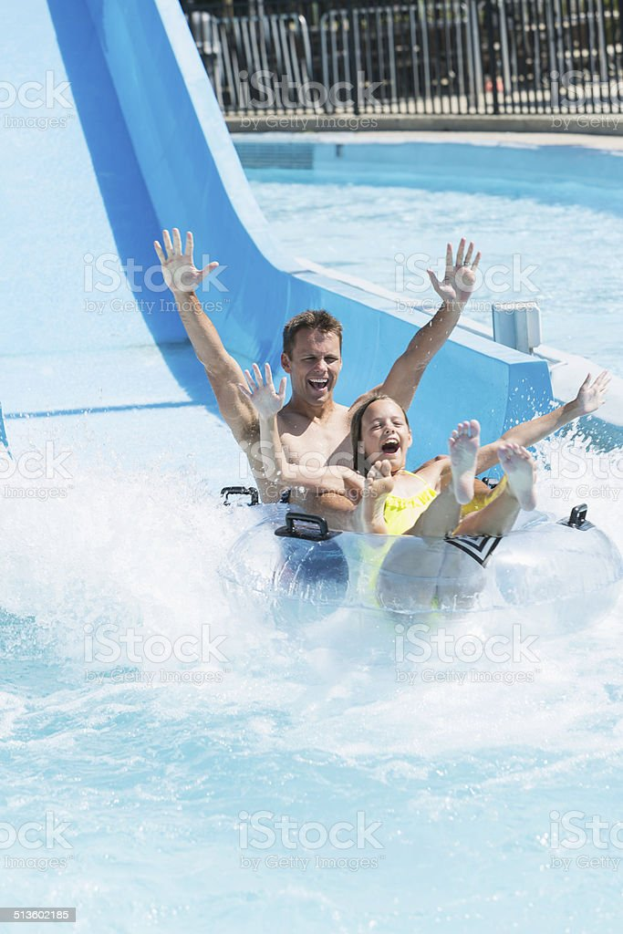 Father and daughter on water slide stock photo