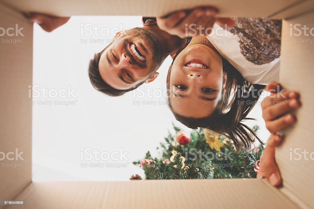 Father and daughter opening a Christmas present stock photo
