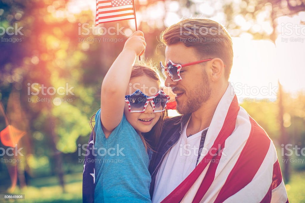 Father and daughter outdoors in a meadow on july 4th. stock photo