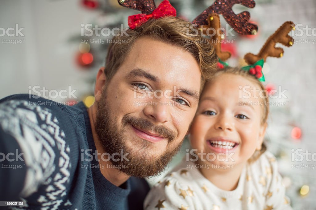 Father and daughter photographing for christmas. stock photo