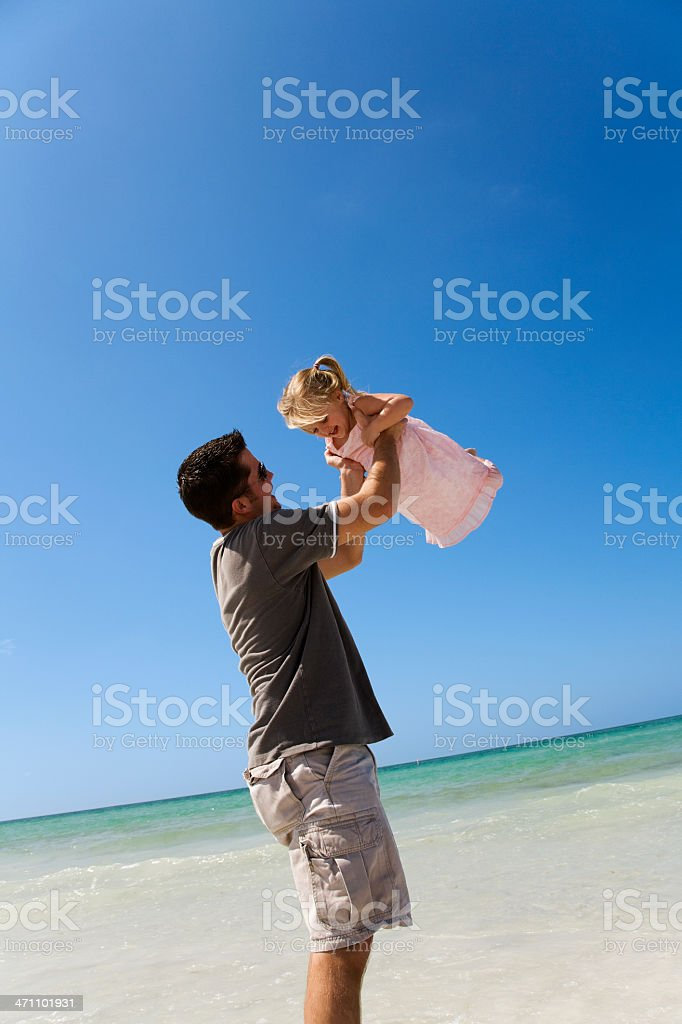 Father and daughter playing at the beach royalty-free stock photo