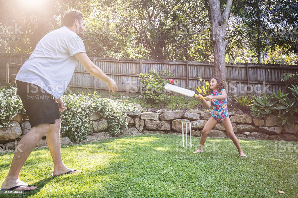 Father and daughter playing cricket in the garden stock photo