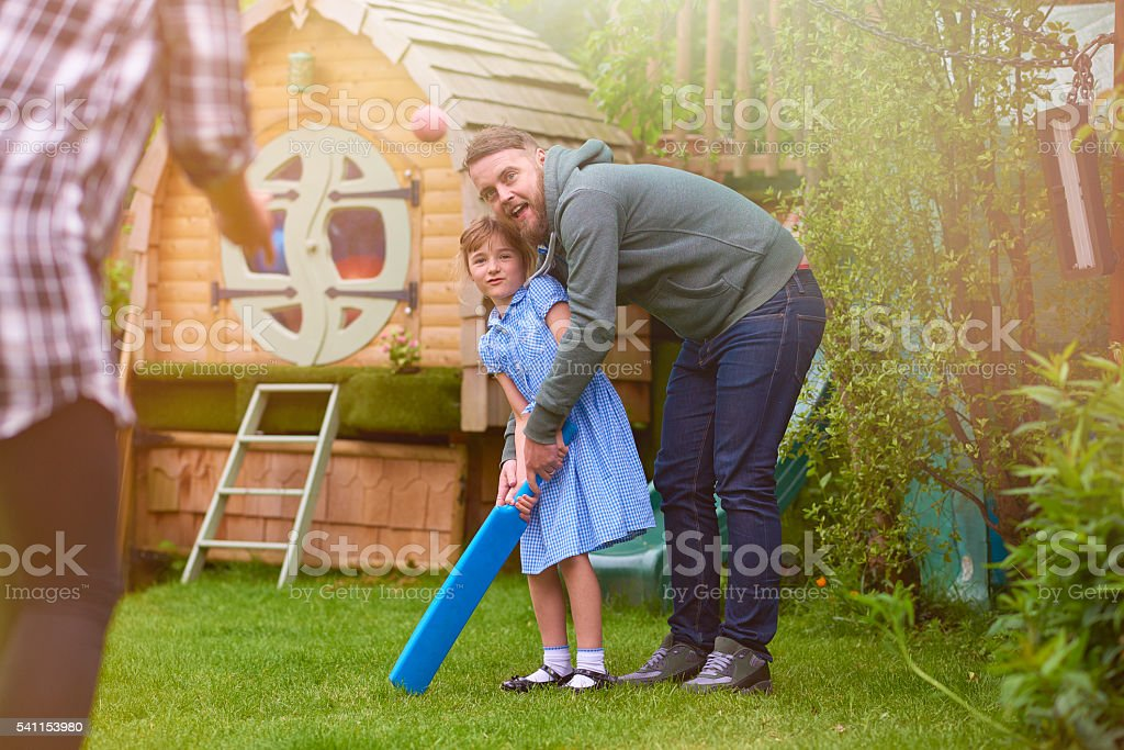 father and daughter playing cricket stock photo