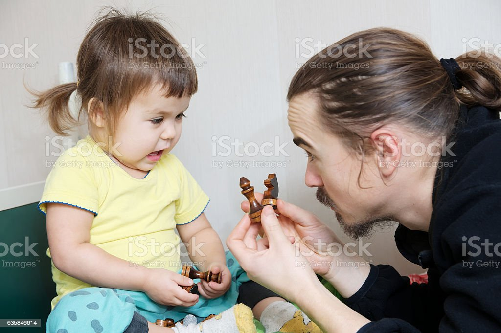 Father and daughter playing, dad teaching child chess figure stock photo
