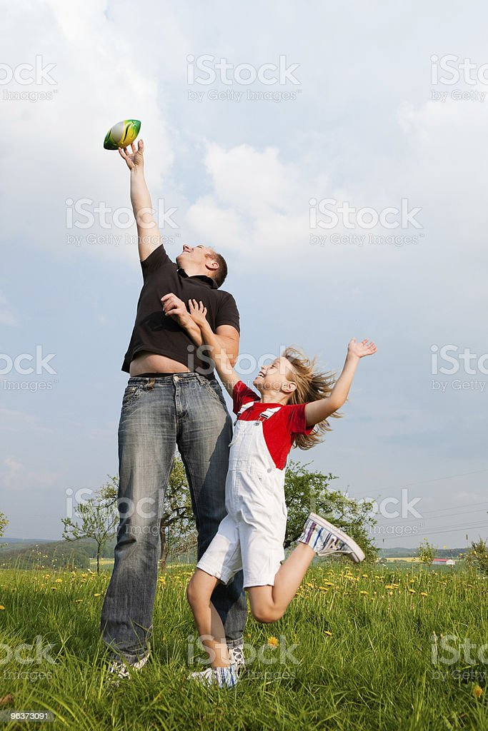 Father and daughter playing football on meadow royalty-free stock photo