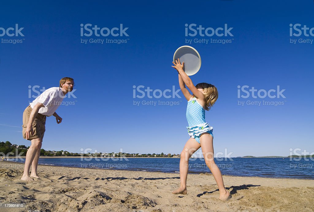 Father and daughter playing frisbee royalty-free stock photo