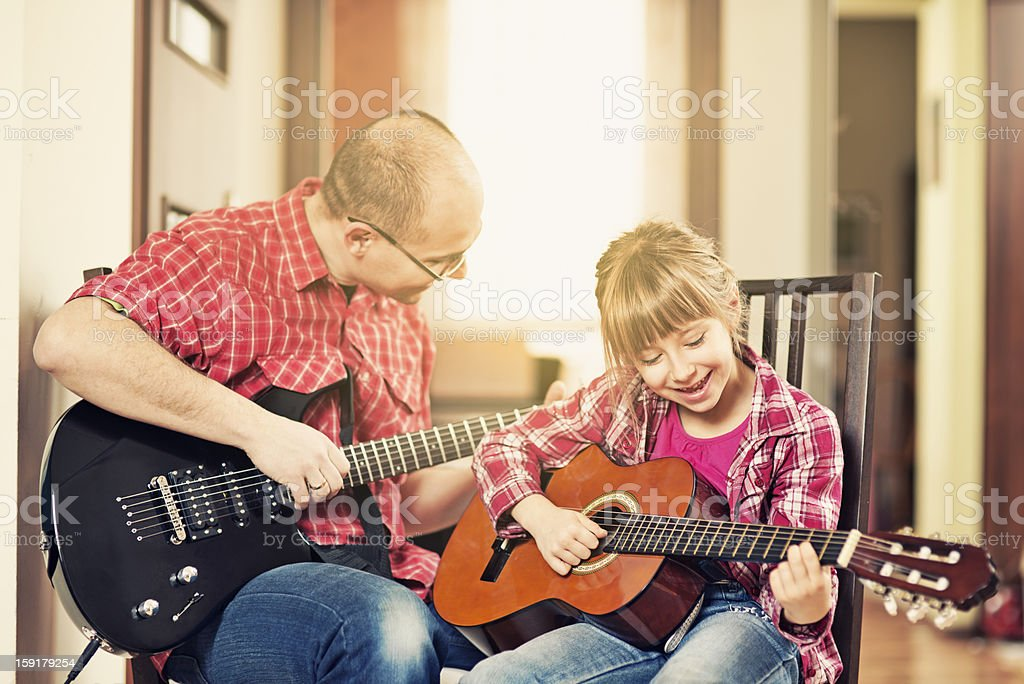 Father and daughter playing guitars together royalty-free stock photo
