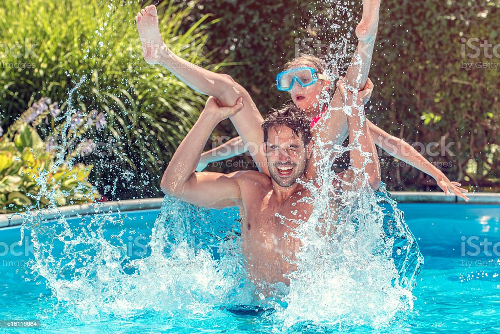 Father and daughter playing in a pool stock photo