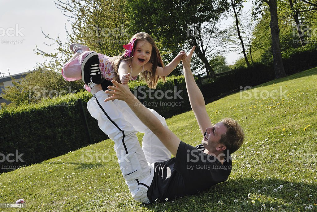 father and daughter playing in garden royalty-free stock photo