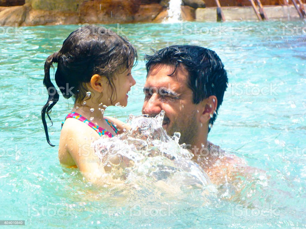 Father and daughter playing in pool stock photo