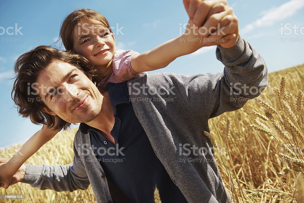 Father and daughter playing in wheat field stock photo