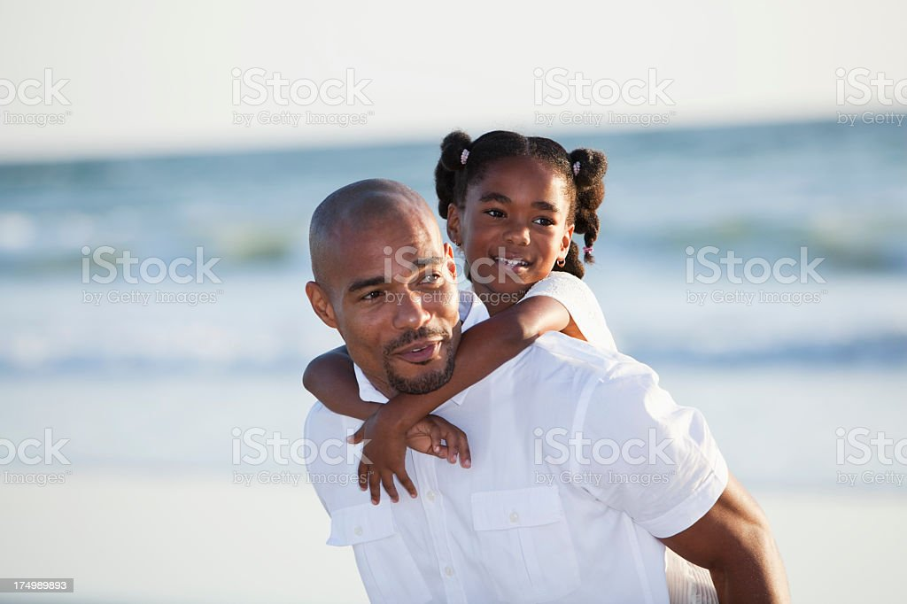 Father and daughter playing on beach royalty-free stock photo