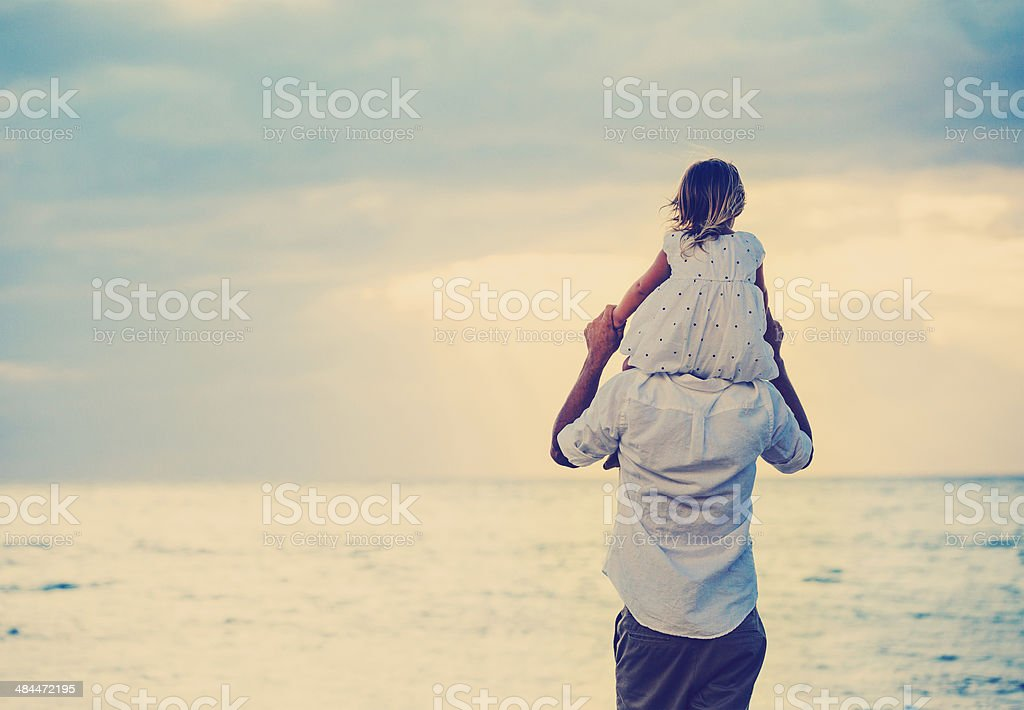 Father and Daughter Playing Together at the Beach at Sunset stock photo