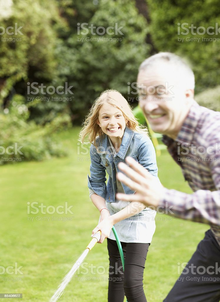 Father and daughter playing with garden hose royalty-free stock photo