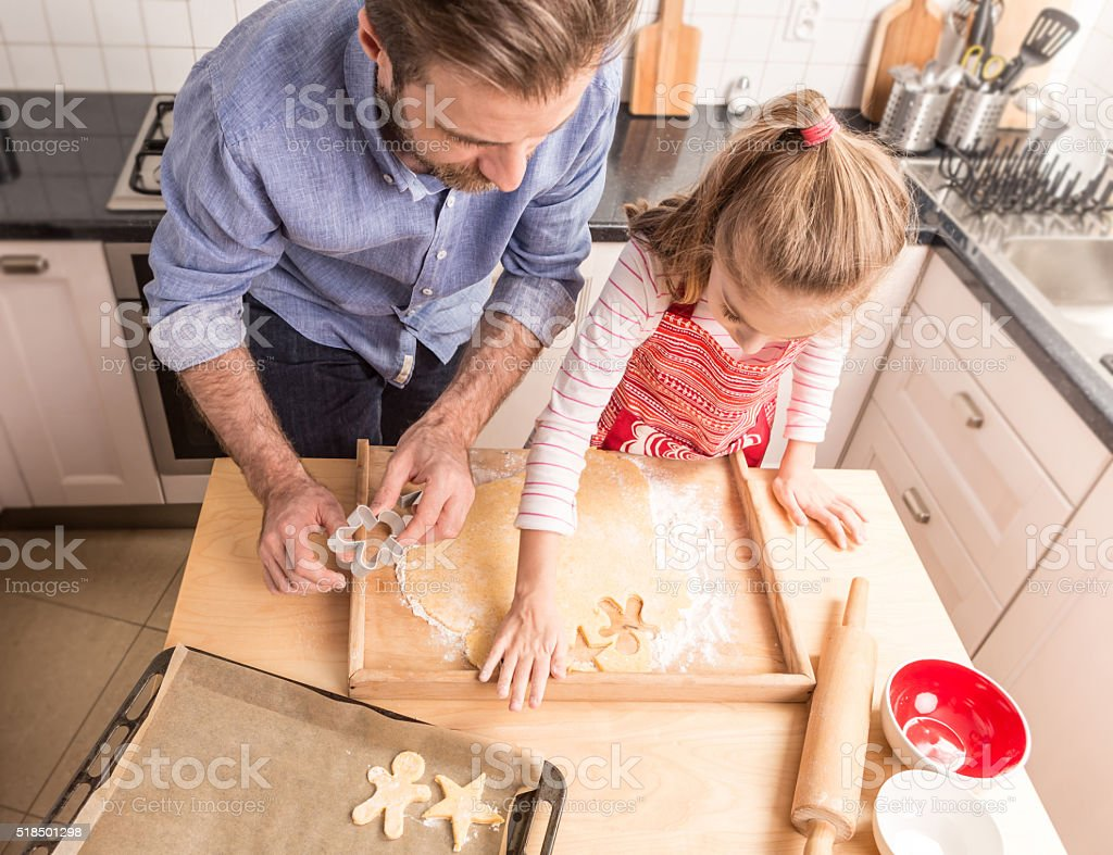 Father and daughter preparing cookies to bake in the kitchen stock photo