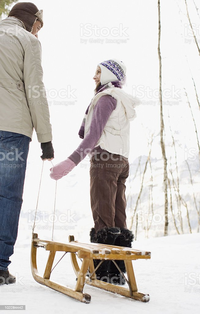 Father and daughter pulling sled through snow royalty-free stock photo