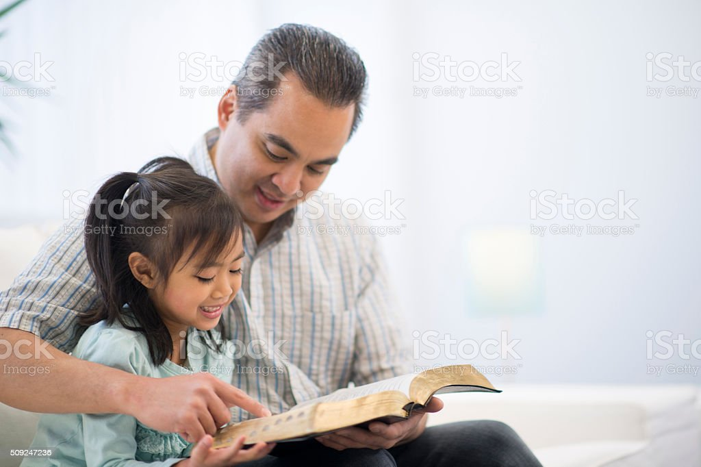 Father and Daughter Reading a Bible Together stock photo