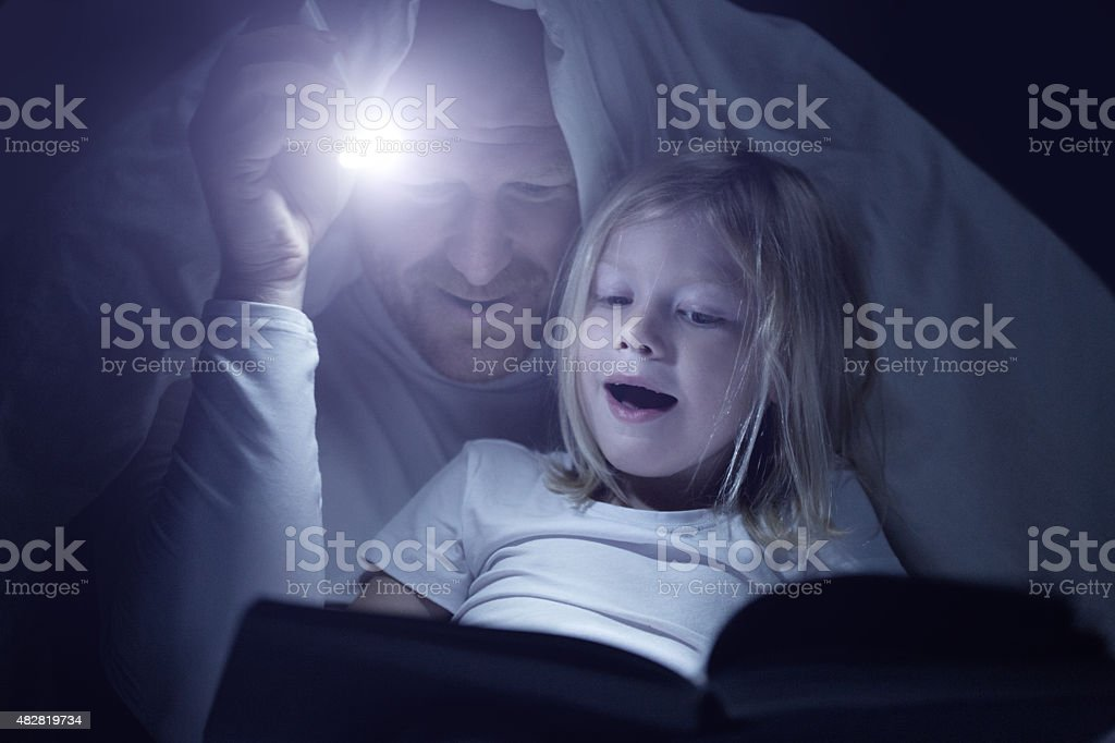 Father and daughter reading book at bedtime stock photo