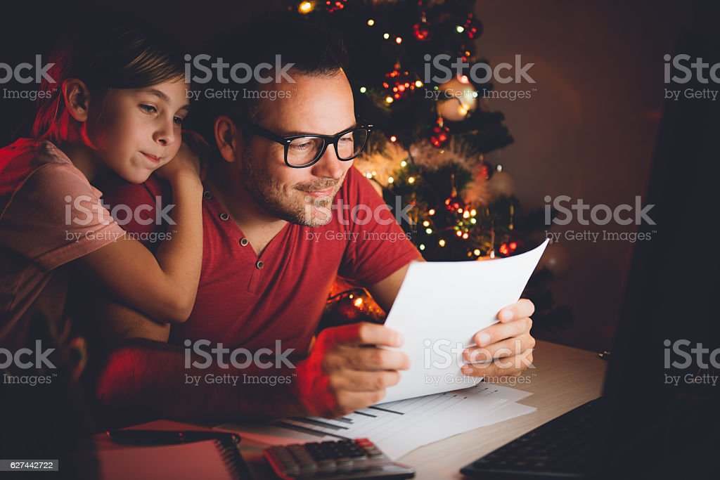 Father and daughter together reading christmas wish list