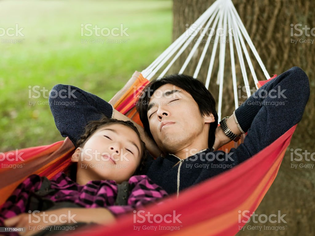 Father and Daughter Relaxing in a Hammock royalty-free stock photo