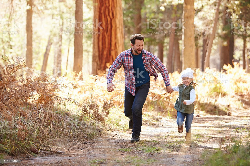 Father And Daughter Running Through Fall Woodland stock photo