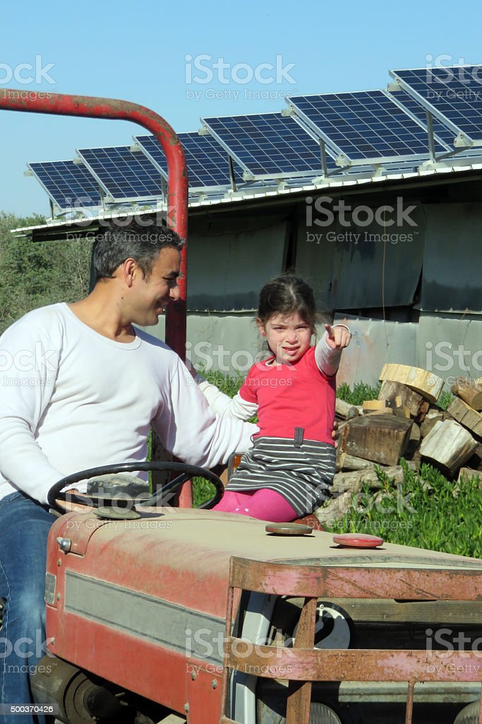 Father and daughter Salafi on a red tractor stock photo