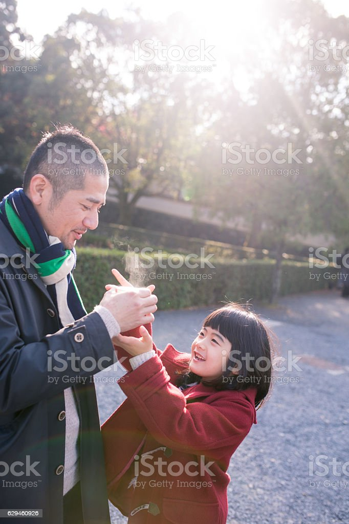 Father and daughter sharing hot tea in the morning stock photo