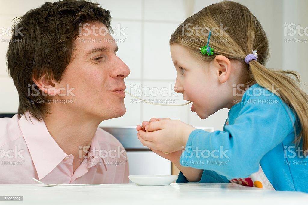 Father and daughter sharing spaghetti stock photo