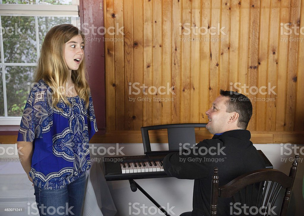 father and daughter singing lesson together in wood panelled room stock photo