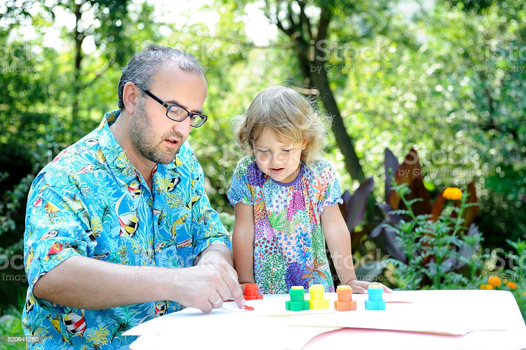 Father and daughter sitting at a table outdoors, draws 1. stock photo