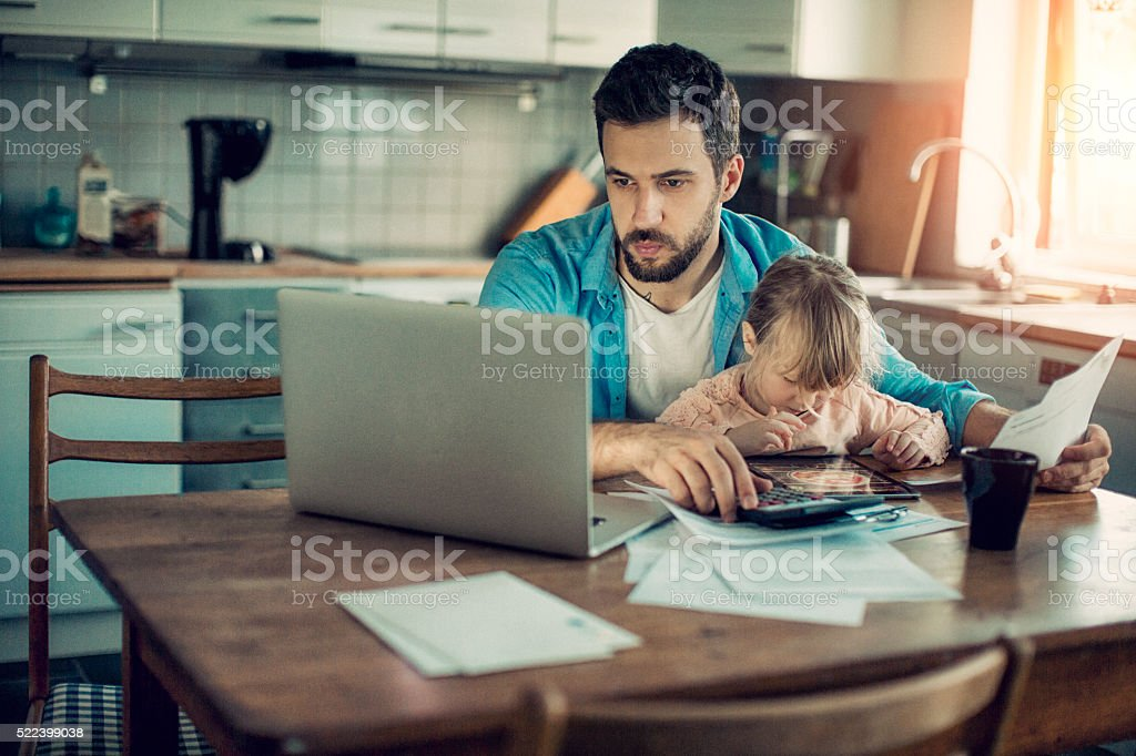 Father and daughter sitting in kitchen stock photo