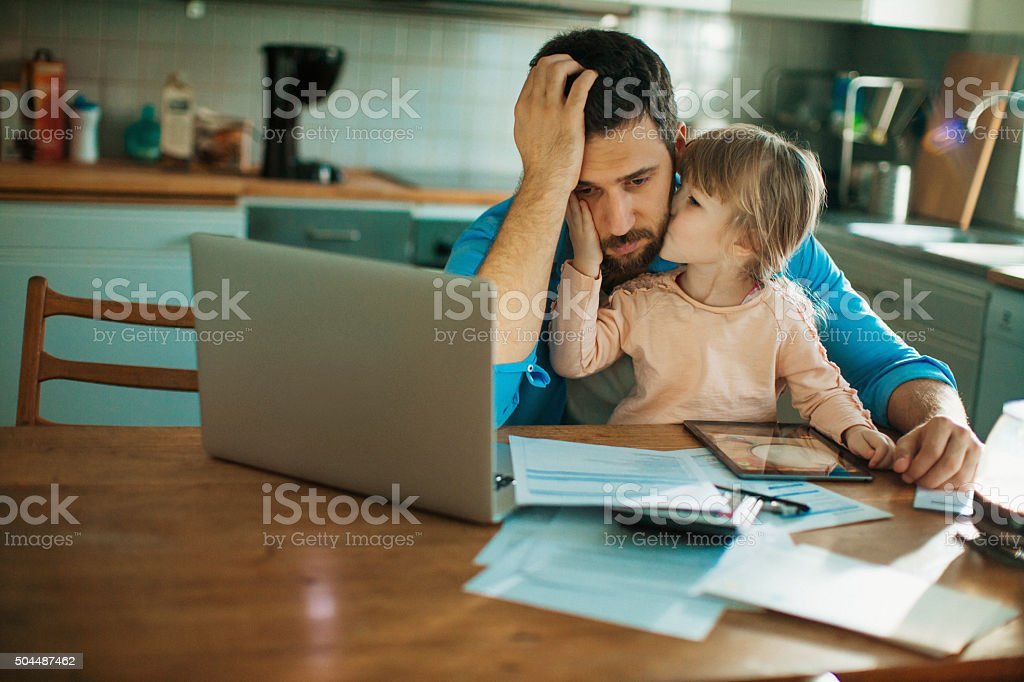 Father and daughter sitting in the kitchen stock photo