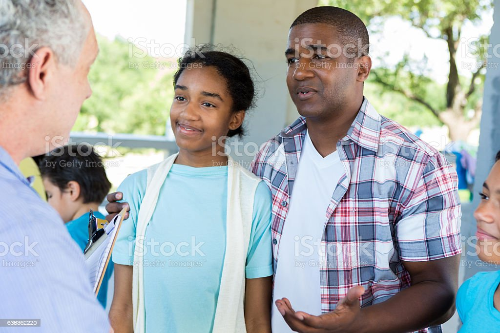 Father and daughter talk with doctor at health fair stock photo