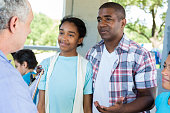 Father and daughter talk with doctor at health fair