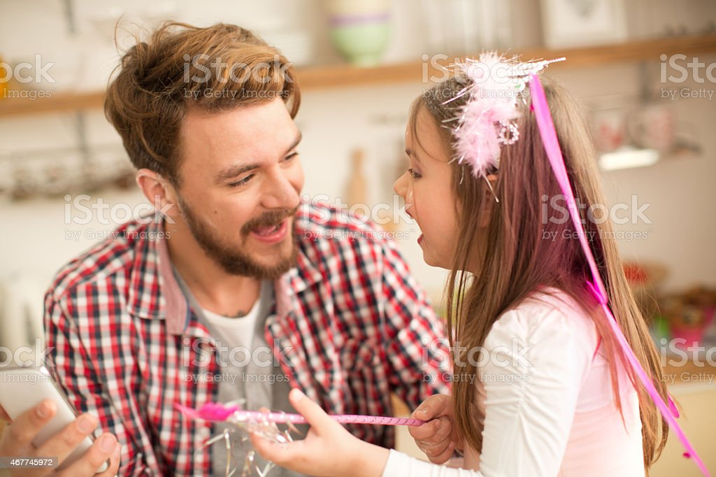 Father and daughter talking in kitchen. stock photo