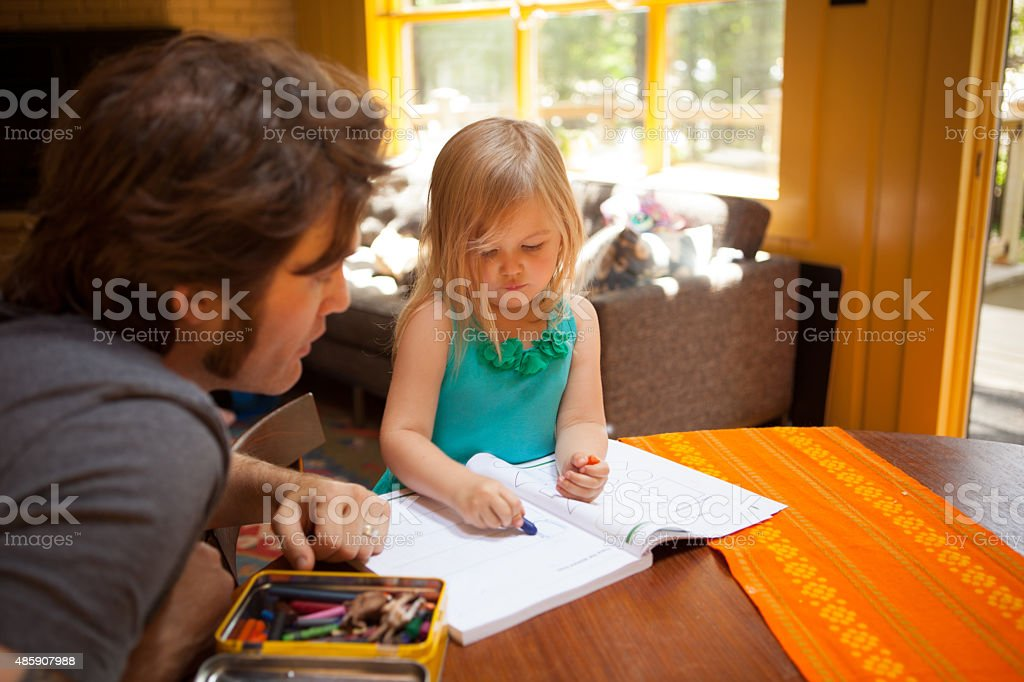Father and daughter tracing shapes in a school book stock photo