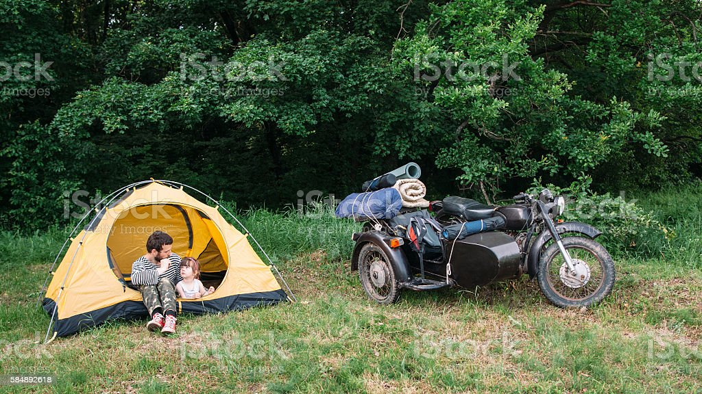 Father and daughter travel on motorbike to camping stock photo