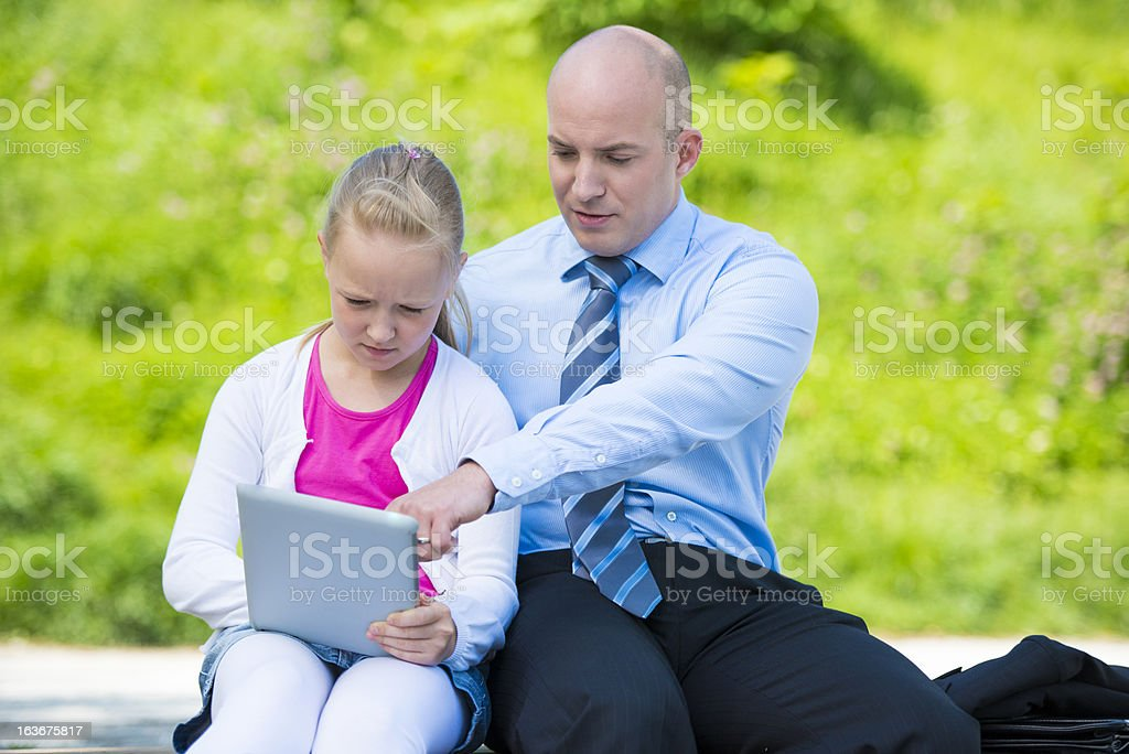 Father and Daughter Using Digital Tablet in the Park royalty-free stock photo