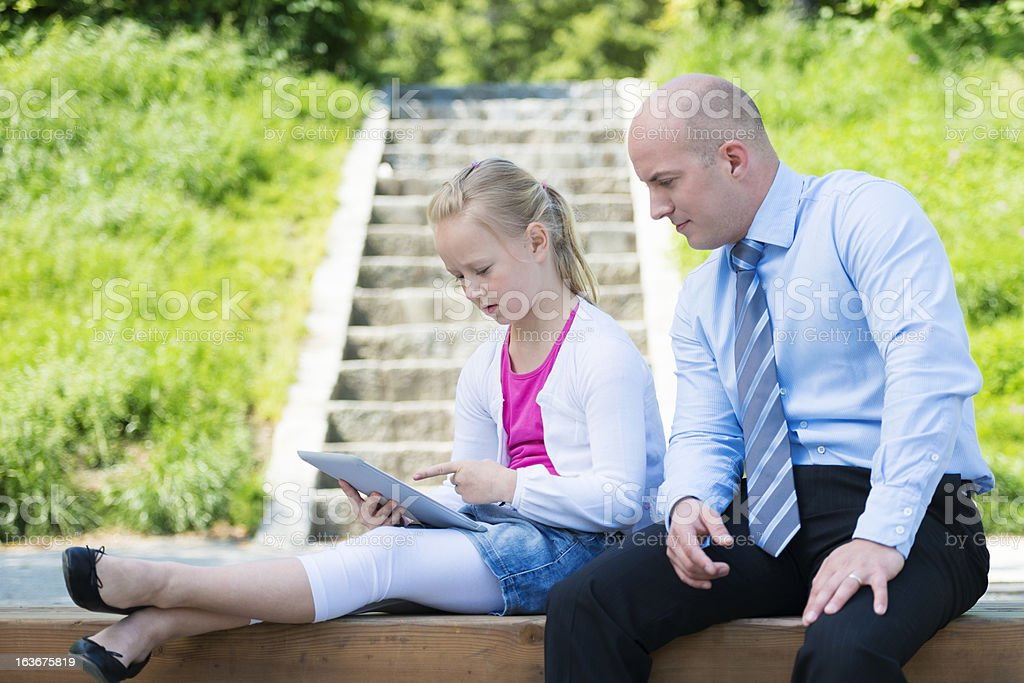 Father And Daughter Using Tablet  In The Park royalty-free stock photo