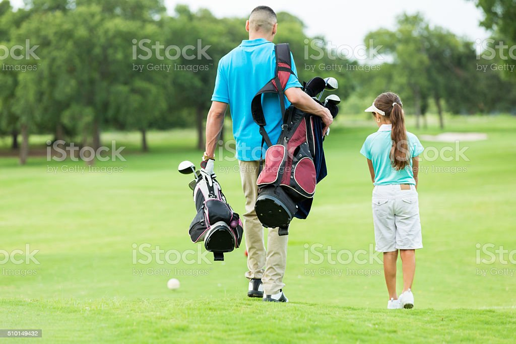 Father and daughter walk on golf course stock photo
