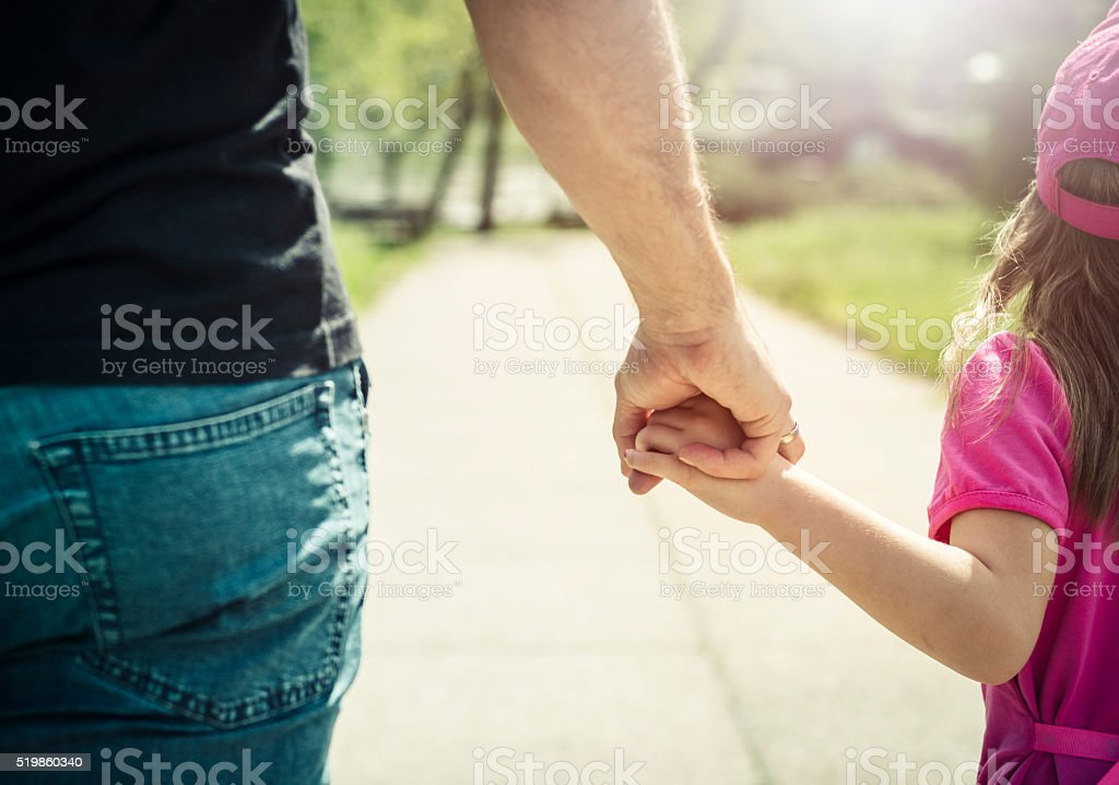 Father and daughter walking and holding hands in park stock photo